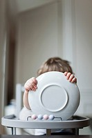 Toddler sitting in high chair, holding plate in front of face (thumbnail)