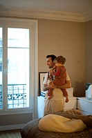 Father holding toddler son, looking out window