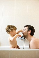 Father and toddler son playing together in the bath