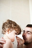 Father helping toddler son blow his nose