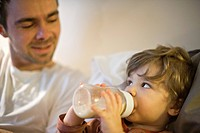Toddler boy with father, drinking milk from baby bottle