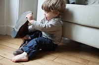 Toddler boy playing with parent's shoes (thumbnail)