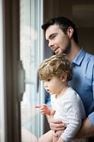 Father and toddler son looking out window, portrait