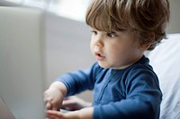 Toddler boy playing with laptop computer, portrait