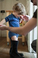 Toddler boy learning to walk in father's boots