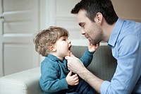 Father examining toddler son's teeth, portrait