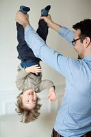 Father holding young son upside down by his ankles