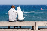 Young couple watching windsurfers at Pozo Izquierdo on Gran Canaria, Canary Islands, Spain