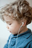 Toddler boy wearing earphones, profile
