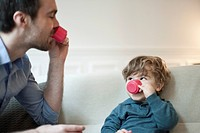 Father and toddler son pretending to drink tea with toy tea cups