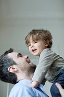Father holding up young son, portrait