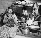 Mid adult Eskimo woman biting a sealskin boot