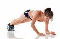 Working out - Woman doing fitness exercise on white floor