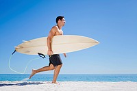 Man carrying surfboard on beach