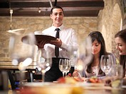 Waiter serving people in restaurant