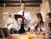 Waiter serving people in restaurant