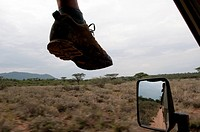 View through a car window of a foot silhouetted against a Kenya plain.