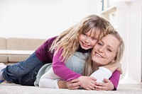 Germany, Bavaria, Munich, Mother and daughter lying at home