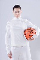 Mid adult woman with basket ball against white background, portrait
