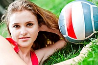 Attractive girl lay on grass with volleyball ball