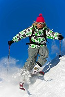 A skier skiing fast through fresh powder snow