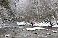 A jogger crossing a snowy alpine river