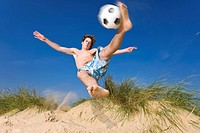 A beach soccer player volleys a ball in mid air