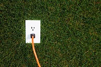 Electrical outlet in grass with extension cord plugged in