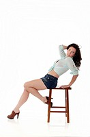 Sexy girl posing on stool in front of white background