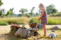 Girl preparing food on grill