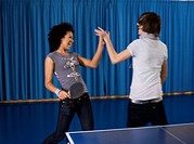 Teenage girl and boy playing table tennis