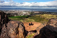 Scotland, City of Edinburgh, Edinburgh. Two women sitting on top of Arthur's Seat taking in the view over Leith and the Firth of Forth