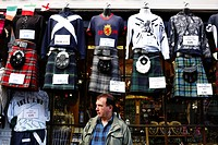 Scotland, City of Edinburgh, Edinburgh. Tartan kilts and Scottish tops hanging outside a shop on The Royal Mile.