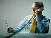 Caucasian businessman covered in cobwebs talking on telephone