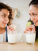 Mother and daughter drinking milk with straws