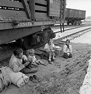 HOMELESS FAMILY, 1939.A destitute farmer with his family seated beside railroad tracks after traveling by freight train to the Yakima Valley, Toppenis...