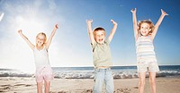 Kids on beach with arms raised
