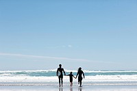 Parents and daughter with surfboard on beach
