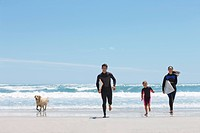 Family with surfboards running on beach