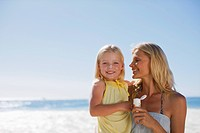 Mother and daughter with sunscreen on beach