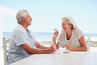Couple playing cards on patio at beach