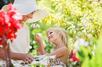 Grandmother and granddaughter picking flowers in garden (thumbnail)