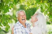 Senior couple laughing under tree