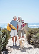 Senior couple with dog walking on beach path