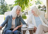 Senior women drinking coffee on patio