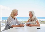 Senior women playing cards on beach patio