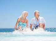 Senior couple splashing in swimming pool