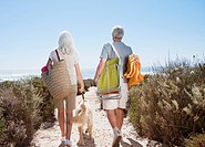 Senior couple walking on beach path with dog