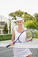 Senior woman holding racket on tennis court