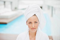 Woman with hair wrapped in towel at poolside
